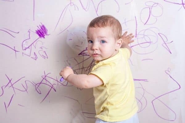 kid scribbling on wall