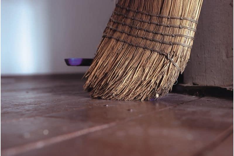 dirty broom on wooden floor